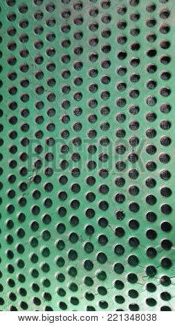 green metal texture with holes. Background with holes.