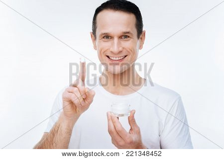 Moisturizing cream. Joyful happy handsome man looking at you and showing you his finger while having moisturizing cream on it