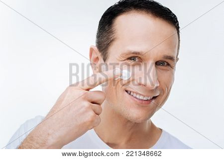 Male cosmetics. Positive nice delighted man smiling and using facial cream while wanting to look handsome