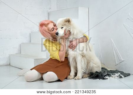 Young girl kissing and hugging a large white friend dog Samoyed. The girl is happy that the dog learned a few training and commands, very intelligent and obedient when trained. coziness and warmth.
