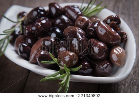 Cured, pickled or brined olive fruit on wooden table