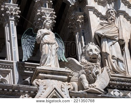Angel with bronze wings at the west facade of the Catehdral of Siena flanked by a lion and philosopher