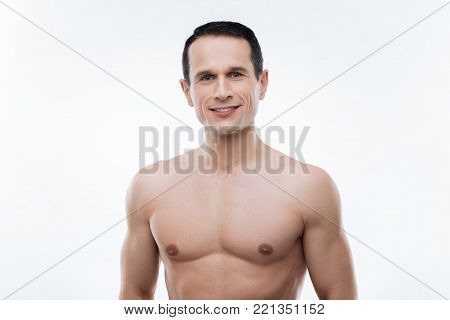 Perfect shape. Delighted nice handsome man standing against white background and smiling while being in the perfect shape