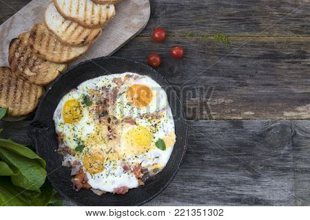 Fried eggs in an old frying pan with cheese, tomatoes, lettuce leaves and fried bread on a wooden background and copy space.