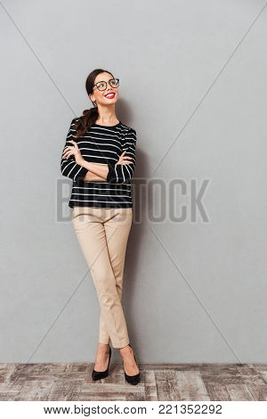 Full length portrait of a smiling businesswoman in eyeglasses standing with arms folded and looking away at copy space isolated over gray background