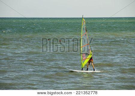 Genichesk, Ukraine - August 25, 2017: Windsurfing. Surfer exercising in calm Azov sea. Recreational water sports during idyllic summer vacation