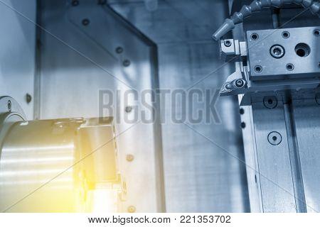The  CNC lathe machine cutting the steel rod in the light blue scene.The CNC lathe machine with the steel bar.
