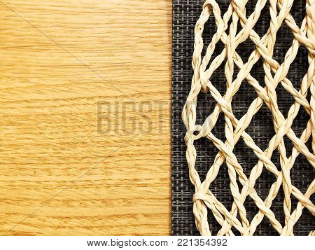 Wickerwork on a wooden background. Close view