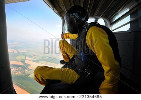 Parachutist in the airplane before jump on sunny day