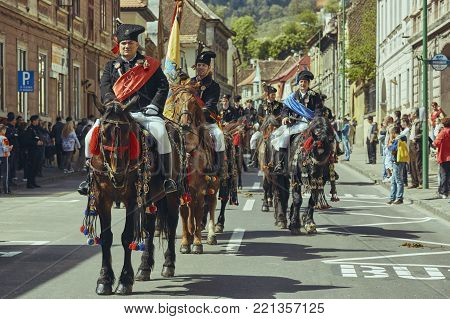 Brasov, Romania - April 27, 2014: Horsemen ride thoroughbred stallions adorned with traditional decorations during the Traditional Parade of the Youths of Brasov.