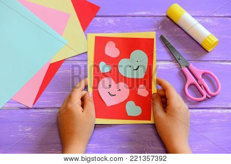 Child is holding a Valentines day card in his hands. Small child made a Valentines day greeting card. Cute and simple paper crafts for kindergarten. Closeup