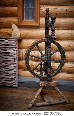 Old wooden spinning wheel in a wooden house stands on the floor