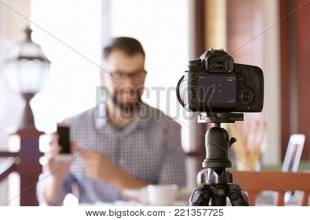 Young blogger recording video in cafe
