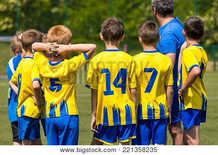 Children soccer team. Kids standing together on the pitch. Youth football coach motivating players before match. Soccer coach speech