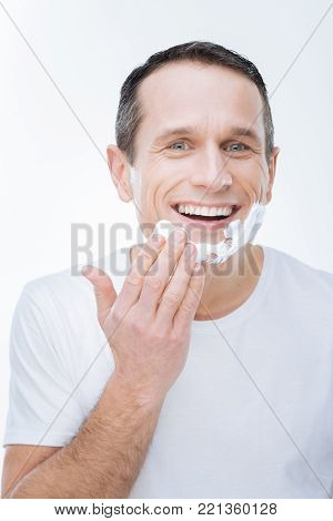 Morning shaving. Joyful handsome young man smiling and putting on shaving foam while being in a good mood