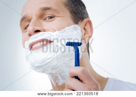 Smooth shaving. Close up of a male razor being in hands of a positive delighted man while shaving