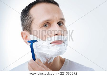 Handsome look. Portrait of a nice pleasant handsome man using a razor while shaving