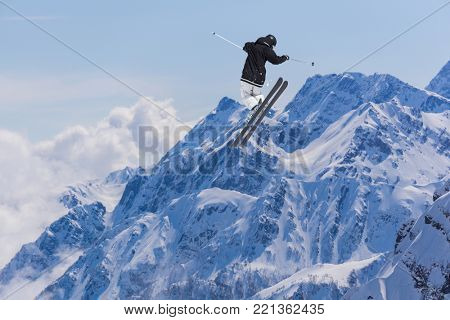 Skier jump in the mountains. Extreme ski sport. Freeride.