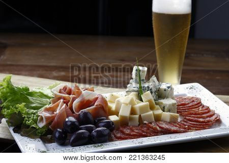 snacks of cold cuts with beer and olive, parma ham, salaminho, and cheeses