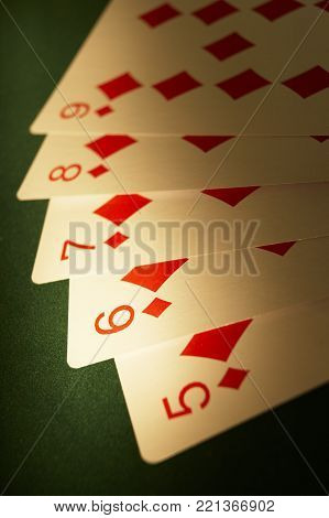 CLECKHEATON, WEST YORKSHIRE, UK: HAND OF PLAYING CARDS SHOWING FLUSH FIVE SIX SEVEN EIGHT OF DIAMONDS ON GREEN CLOTH GAMING TABLE, CIRCA 2007, CLECKHEATON, WEST YORKSHIRE, UK