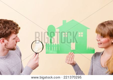 Housing real estate family future finances concept. Young pair give attention to details. Just married man with woman taking magnifying glass to look closer at house model.