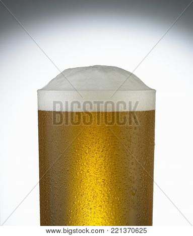 GLASS OF COLD BEER WITH FROTHY HEAD AND CONDENSATION DROPLETS CLOSE UP