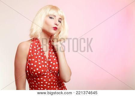 Vintage pinup style. Portrait of beautiful stylized young woman flirting blowing a kiss. Attractive girl in blond wig and retro spotted red dress on pink. Disguise. Studio shot.