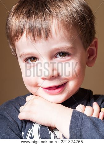 portrait of 4 year old child while smiling lit by sunlight