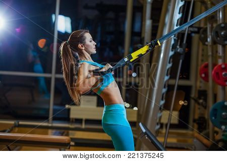 Beautiful muscular woman doing exercise with trx system. Young woman exercising with suspension trainer at gym