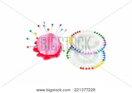 Pillow for needles and bright colored pins isolated on white background. A set of sewing accessories.