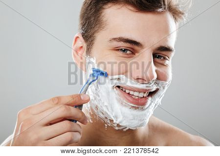 Photo of masculine brunette guy with dark short hair shaving his face with razor and gel or cream, being satisfied over grey background close up