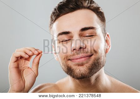 Close up portrait of a satisfied man cleaning his ears with a cotton swab isolated over gray background