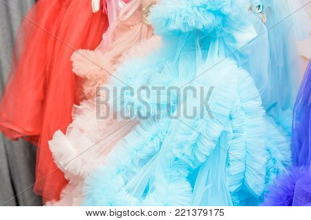 Close-up image of bright colorful dresses hanging on rack in changing room
