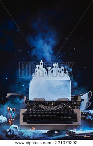 Fantasy writer workplace with a typewriter and paper castle. Fortress of an imagination. Creative writing concept. Dark background with copy space.