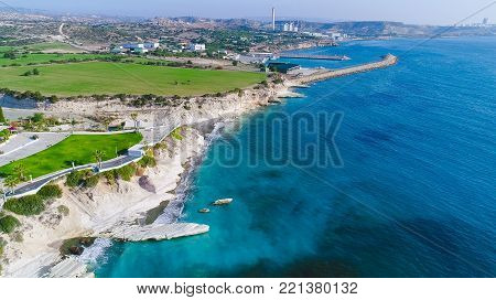 Aerial view of coastline and landmark big white chalk rock at Governor's beach, Limassol, Cyprus. The steep stone cliffs and deep blue sea waves crushing in coves and dark sand at Kalymnos from above and vasilikos power station.