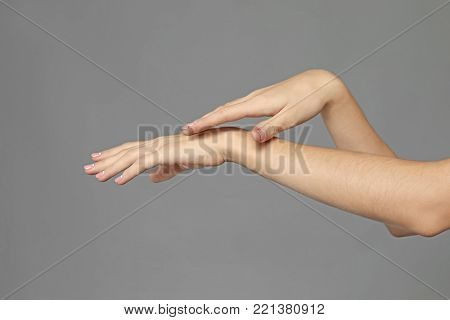 Hands of young woman with healthy skin softened by cream with moisturizing effect, on grey background