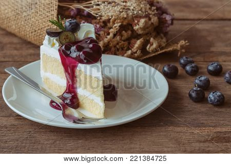 Blueberry cream cake on white plate. Homemade blueberry cake on wood table in side view. Vanilla sponge cake decorated with dairy whipped cream and blueberry sauce so soft sweet and delicious. Homemade bakery background. Blueberry cake ready to served.