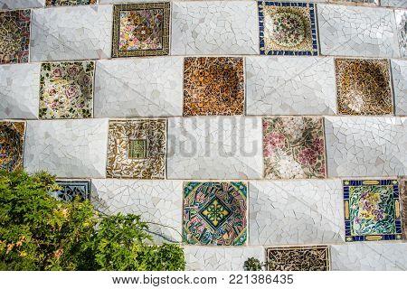 BARCELONA, SPAIN - FEB. 16: Closeup of mosaic of colored ceramic tile by Antoni Gaudi at his Park Guell, Barcelona, Spain, on February 16 2017 in Barcelona Spain