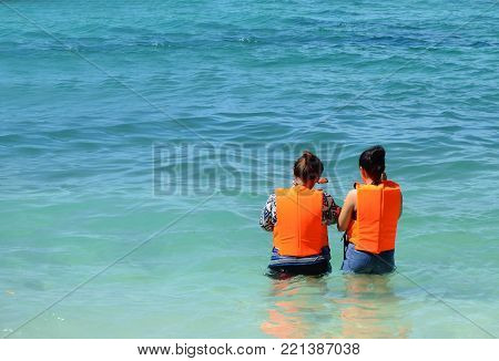 Couple of  asian woman teenager with life-jackets is going to dive in blue sea during their holiday