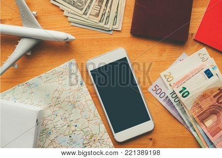 Overhead view of vacation travel concept with smartphone blank screen as mock up copy space for hotel reservation and booking mobile app or airplane ticket purchase application.