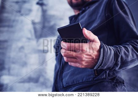 Low angle view of casual adult man reading private SMS text message on his personal mobile phone, ultra violet toned shadows
