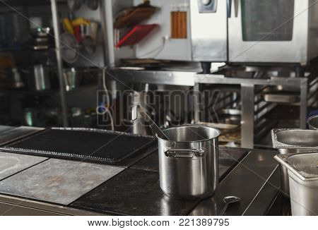 Profesional hotel or restaurant kitchen interior. Stainless steel pot on hotplate in foreground