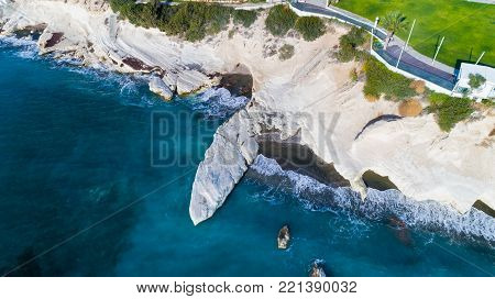 Aerial view of landmark big white chalk rock at Governor's beach, Limassol, Cyprus. The steep stone cliffs and deep blue sea waves crushing in coves and dark sand next to Kalymnos fish restaurant from above.
