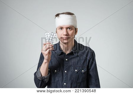 Injured young man with bandage on his head holding anesthetic pills. Image related with treatment of the wounds