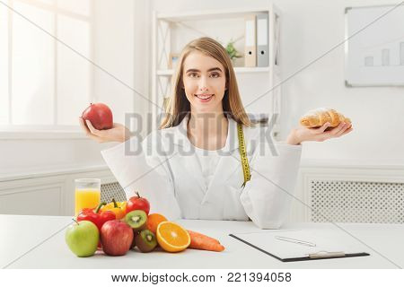 Dietitian with bun and fresh apple. Woman nutritionist holding fruit and croissant comparing junk and healthy food. Right eating nutrition concept.