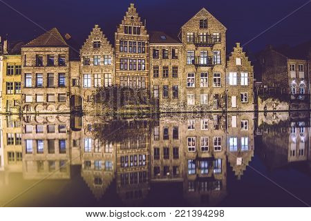 Ghent, Flanders, Belgium - January 2th, 2017. Night Gent Old town view with illuminated medieval merchant houses reflected on the water of canal by evening lights. City illumination.