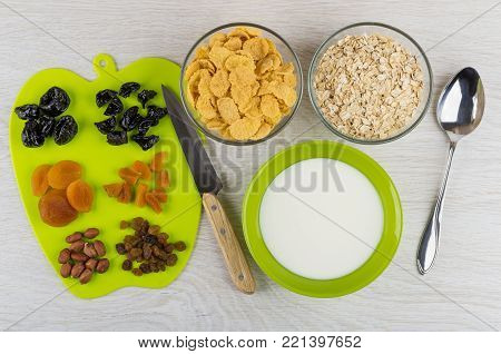 Chopped dried fruits and peanuts on cutting board, bowls with corn flakes, oat flakes and yogurt, knife and spoon on wooden table. Top view