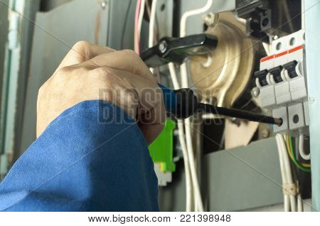 Hand of electrician working with screwdriver in cables and wires in fuse box. Electrical background.