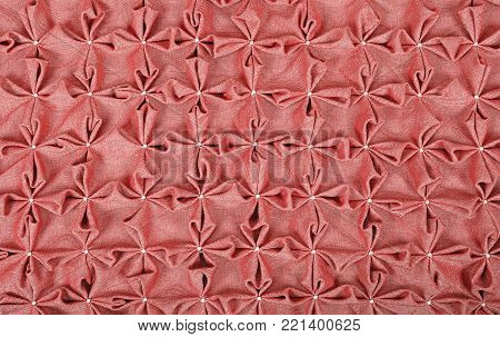 Close up background texture of pink red textile puffs for Canadian smocking upholstery decoration with beads