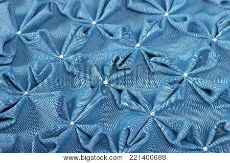 Close up background texture of soft blue textile puffs for Canadian smocking upholstery decoration with beads